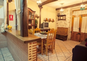 Salón comedor con muebles y televisor visto desde la cocina