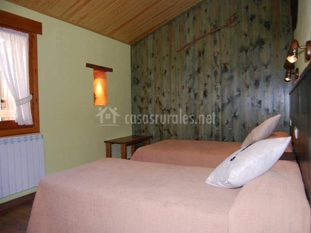 Dormitorio con camas individuales y paredes de madera