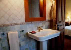 Baño azul con mosaico grande y espejo de madera sobre el lavabo blanco
