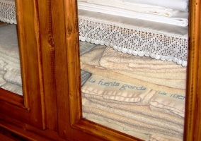 Toallas en el armario de madera grabadas con el nombre de la casa