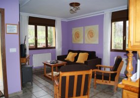 Salón morado con sofá y sillas marrones