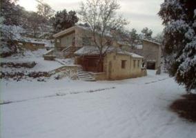 Patio exterior con nieve, mesa, bancos y barbacoa