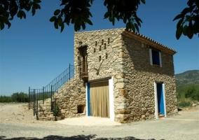 Fachada de piedra y fuente de las dos edificios de la casa rural