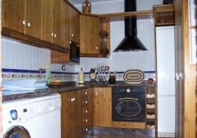 Cocina de madera oscura y electrodomésticos