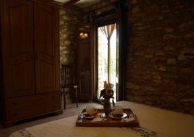 Contra luz en el dormitorio de matrimonio con bandeja del desayuno y pared de piedra