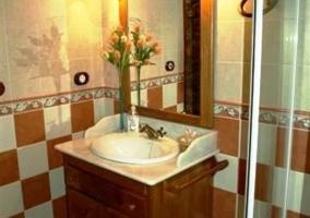 Detalle del lavabo con azulejos de cuadros naranjas y blancos