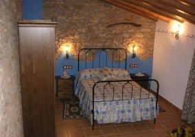 Dormitorio azul con pared de piedra y techo abuhardillado