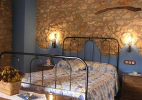 Dormitorio de matrimonio con cabecero de hierro y pared de piedra