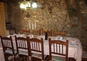 Mesa puesta en la sala multiusos con pared de piedra de la casa rural