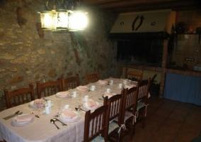 Mesa puesta en la sala multiusos con barbacoa de la casa rural