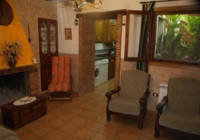 Sala de estar con chimenea y cocina al fondo en la casa rural
