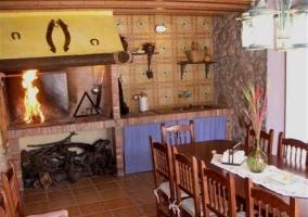 Sala multiusos con barbacoa encendida y mesa de madera amplia