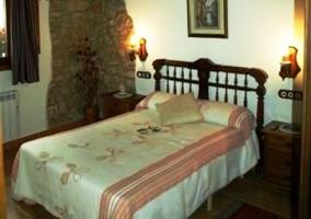 Vista del dormitorio de matrimonio con edredón blanco y rosa en la casa rural