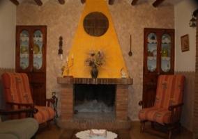 Vista frontal de la chimenea del salón de la casa rural