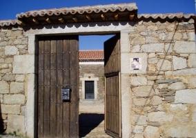 Acceso a la vivienda con fachada en piedra y zonas verdes