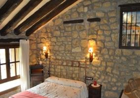 Sala común con pared de piedra y techo de madera