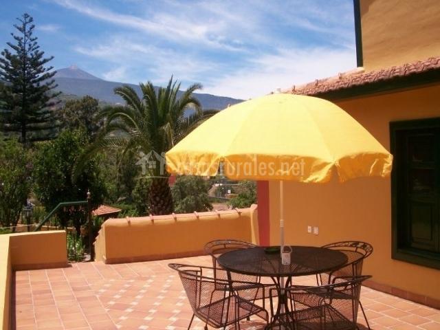 Acceso con terraza y muebles bajo la sombrilla