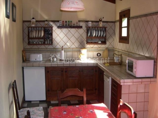 Cocina en L con mesa para comer y sillas