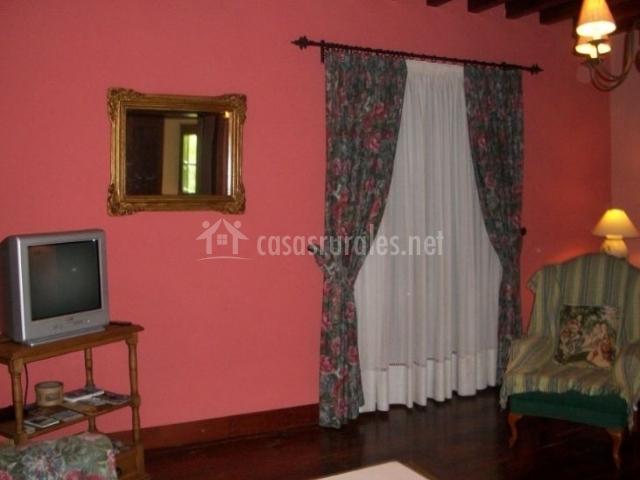 Sala de estar con sillones tapizados de flores y televisor