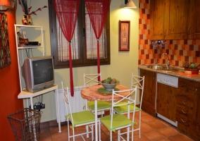 Cocina con mobiliario y televisión