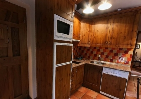 Cocina con muebles de madera y azulejos naranjas