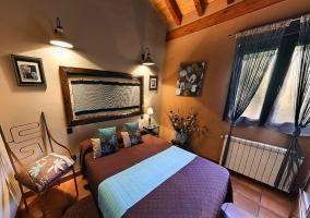 Dormitorio de matrimonio con techo abuhadllado y cama morada y azul