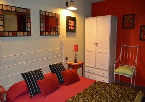 Dormitorio de matrimonio rojo con armario blanco