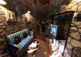 Salon con paredes de piedra y chimenea Sillones azules