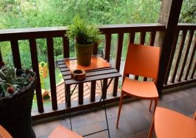 Terraza con mobiliario naranja y barandilla de madera