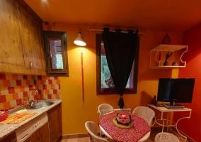 Zona de comedor y cocina con mesa y sillas