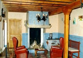Salón con chimenea y columnas de madera de casa rural