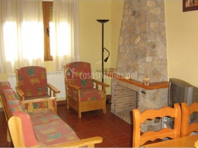 Salón con sofá rojo y dos butacas además de chimenea de ladrillo y televisión