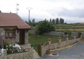 Vista general de la fachada de la casa rural con jardín de césped natural