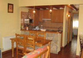 Cocina americana con muebles de madera marrón y barra de bar de marmol unida a una zona de comedor con mesa y cuatro sillas