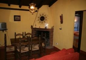 Salón con sillón rojo, mesa de comedor y chimenea