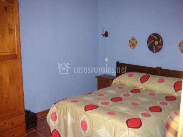 Dormitorio con cama de matrimonio y paredes en azul