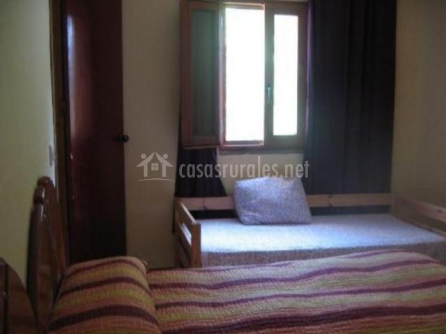 Dormitorio con su ventana y cortinas