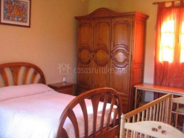 Dormitorio de matrimonio con mesilla de madera y cuna