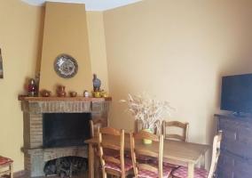 Sala de estar con la chimenea en la esquina y mesa de madera