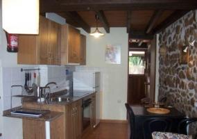 Cocina con muro lateral en piedra y armarios de madera