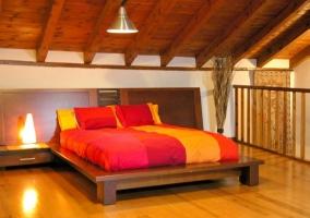 Dormitorio de matrimonio de la casa rural con techo abuhardillado de madera