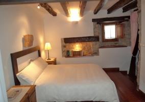 Dormitorio con cama de matrimonio de la casa rural decorado en madera oscura y blanco