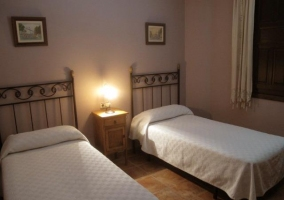 Dormitorio doble con colchas blancas en casa rural