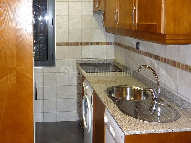 Cocina completa con lavadora y ventana al fondop
