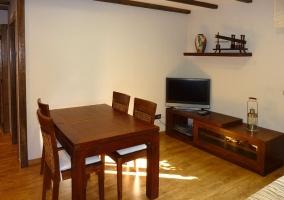 Sala de estar y comedor con una mesa de madera con sillas