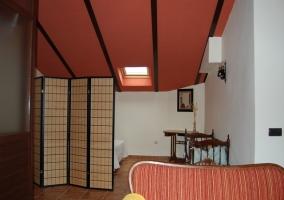 Dormitorio abuhardillado con techo rojo