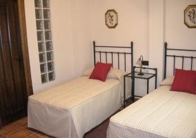 Dormitorio con dos camas individuales y cojines rojos