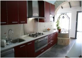 Cocina roja iluminada con un pequeño pozo