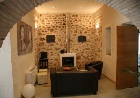 Sala de estar con chimenea y acceso desde el arco de piedra del salón