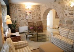 Salón con paredes de piedra y mesa de cristal